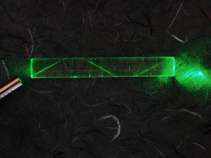 A laser beam through acrylic shows the concept of total internal reflection (the light doesn't continue straight through the edge of the glass, but bounces back and forth until exiting at the end).